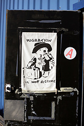 18 November 2020. Care4Calais - Calais, France.<br /> Care4Calais warehouse. 'Migration is not a crime,' reads the poster of Paddington Bear - himself an immigrant to the UK from Peru adorns the back of a door at the charity's distribution hub.  Everything donated to the charity which can be used is cleaned, pre sorted and checked to ensure items are in good condition before they are distributed to desperate migrant refugees - many of whom have little in the way of warm clothing or possessions as winter approaches.<br /> Claire Moseley, founder of the British volunteer run refugee charity Care4Calais works tirelessly to build her foundation  to help migrant refugees as they struggle to survive on the streets of Calais where they are constantly harassed and moved on by authorities. Care4Calais provides meals, clothing, haircuts, charging stations for phones, medical aid, hot drinks, tents, blankets and a wide range of goods and services.<br /> Photo©; Charlie Varley/varleypix.com