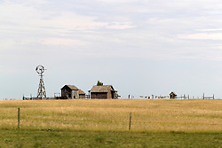 A few old buildings and an old windmill still stand on the prairie