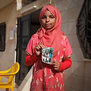 """Manar, 13, and her family arrived in Jordan two years ago, from Homs, Syria. Manar, like Halaa, just finished the tailoring program through the Mercy Corps project """"No Lost Generation."""" """"I was enrolled in school when I first arrived here. They sent my brother back to Syria, so I had to leave school to help at home. I miss school. Next year I hope to return.""""<br /> <br /> She has two brothers in Syria. One of them didn't have papers to allow him to cross the border into Jordan and the other was caught working, which is illegal for refugees. """"When they were bombing in Homs, we were so afraid. These photos are from when I was little. We brought a lot of things with us, but they didn't let us bring our things across the border."""" Manar managed to bring her photos across, which remind her of her family. Mafraq, Jordan, May 2015."""