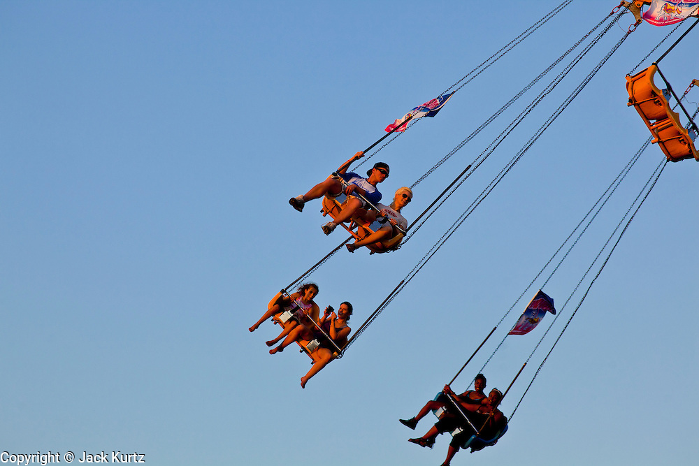 """01 SEPTEMBER 2011 - ST. PAUL, MN:  People on the Sky Flyer on the midway at the Minnesota State Fair. The Minnesota State Fair is one of the largest state fairs in the United States. It's called """"the Great Minnesota Get Together"""" and includes numerous agricultural exhibits, a vast midway with rides and games, horse shows and rodeos. Nearly two million people a year visit the fair, which is located in St. Paul.   PHOTO BY JACK KURTZ"""