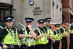© Licensed to London News Pictures. 01/06/2018. Leeds, UK. Police guard the entrance to Leeds Crown Court . Supporters of EDL founder Tommy Robinson ( real name Stephen Yaxley-Lennon ) demonstrate in Leeds after Robinson was convicted of Contempt of Court . Robinson was already serving a suspended sentence for Contempt of Court over a similar incident , when he was convicted on Friday 25th May 2018 . Reporting restrictions , since lifted , initially prevented coverage of Robinson's arrest and incarceration . Photo credit: Joel Goodman/LNP