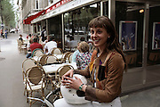 Alexandra Boulat seated astride her motorbike and holding her helmet, in front of a cafe. Paris, France.  MODEL RELEASED.