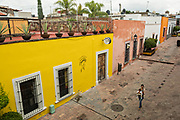 A woman walks down a colorful alley in the old colonial section of Santiago de Queretaro, Queretaro State, Mexico.