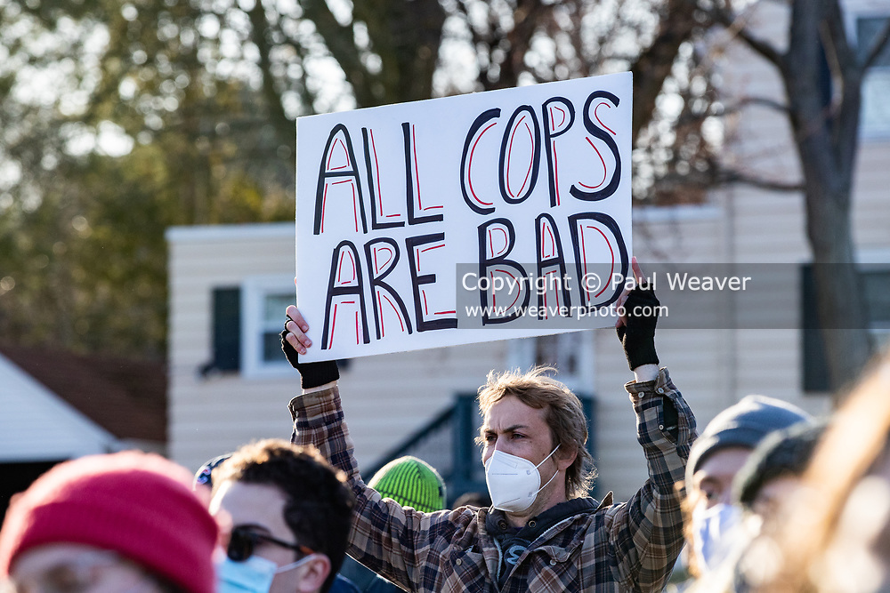 """A protester holds a sign reading """"all cops are bad."""""""