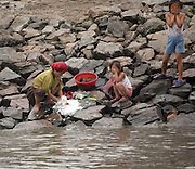 A woman does her washing with her daughters nearby in the North Korean border town of Sunuiju Ocotber 10, 2006. North Korea's nuclear weapons are not yet developed or sophisticated enough to put on a missile, and military pre-emption isn't a viable strategy. Any attack aimed at destroying Kim's weapons would likely unleash North Korea's million-man army, poised just miles from the South Korean capital and the 28,000 U.S. troops stationed nearby... DPRK, north korea, china, dandong, border, liaoning, democratic, people's, rebiblic, of, korea, nuclear, test, rice, japan, arms, race, weapons, stalinist, communist, kin jong il