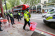 A police officer helps to clean the colour after a group of Protestors pelted in red colour (resembling blood) the Office of Israeli arms company, Elbit System in London on Saturday, Oct 10, 2020. Elbit Systems openly market their weapons as 'field-tested' on Palestinian civilians in Gaza. (VXP Photo/ Vudi Xhymshiti)