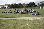 A group of teenagers in a school group sitting on grass eating a picnic lunch, Suffolk, England, UK