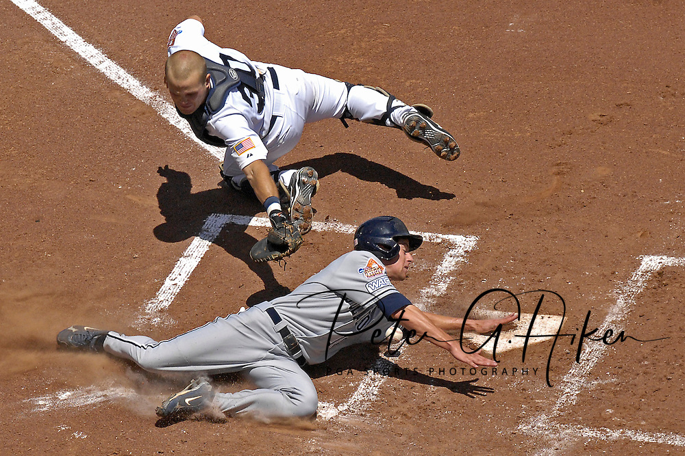 Fresno State Bulldogs shortstop Danny Muno (16) slides and scores a run around the attempted tag at home plate by Rice Owls catcher Adam Zornes (30) during the College World Series at Rosenblatt Stadium in Omaha, Nebraska.