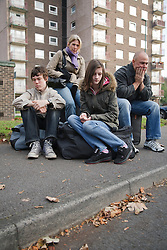 Homeless family who have just been evicted sit dejectedly outside their former home