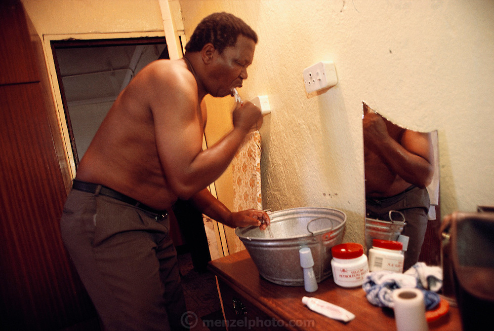 Simon Qampie brushes his teeth over a bucket in the bedroom of his family's house in Southwest Township (called Soweto), South Africa. They have running water in the kitchen only, and their toilet is an outhouse in their backyard. The Qampie family lives in a 400 square foot concrete block duplex house in the sprawling area of Soweto, outside Johannesburg (Joberg) South Africa. Material World Project.