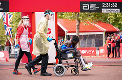 An athlete is attended to by staff after finishing the Women's elite race during the Virgin Money London Marathon. Picture date: Sunday October 3, 2021.