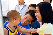Hmong mom and dad cheer son after being treated in health care tent. Hmong Sports Festival McMurray Field St Paul Minnesota USA