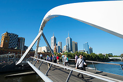 Pedestrians crossing Southbank Footbridge across Yarra River in central Melbourne Australia