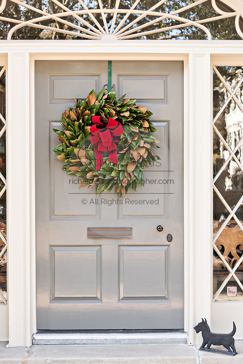 The wooden doorway of a historic home decorated with a Magnolia leaf Christmas wreaths on Meeting Street in Charleston, SC.