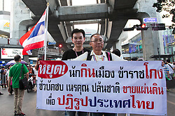 © Licensed to London News Pictures. 05/01/2014. Anti-Government protestors hold a banner reading anti-government rhetoric during the third day of the 'Bangkok Shutdown' as anti-government protesters continue with their 'shutdown' of Bangkok.  Major intersections in the heart of the city have been blocked in their campaign to oust Prime Minister Yingluck Shinawatra and her government in Bangkok, Thailand. Photo credit : Asanka Brendon Ratnayake/LNP