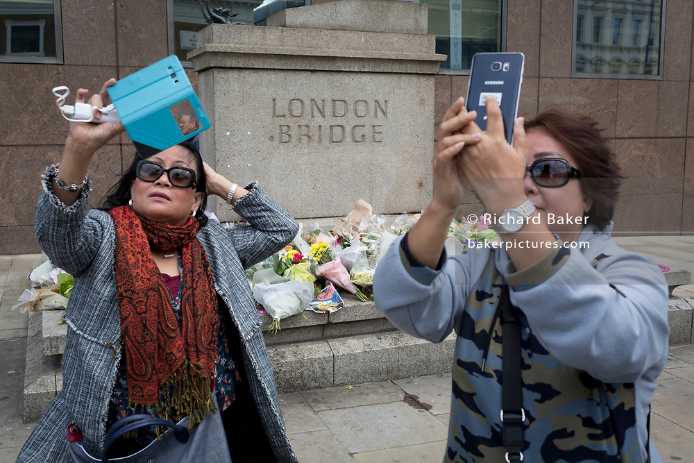 Three days after the terrorist attack in which 7 people died and many others suffered life-changing injuries on London Bridge and Borough Market, tourists take tragedy selfies by the shrine of flower tributes, on 6th June 2017, on London Bridge, in the south London borough of Southwark, England. City commuters now back at work walk respectfully and quietly past the floral memorial at the plinth marking the southern boundary of the City of London, the capital's financial district.