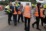Metropolitan Police officers move Insulate Britain climate activists out of a slip road from the M25 at Junction 25 which they had blocked as part of a campaign intended to push the UK government to make significant legislative change to start lowering emissions on 15th September 2021 in Enfield, United Kingdom. The activists, who wrote to Prime Minister Boris Johnson on 13th August, are demanding that the government immediately promises both to fully fund and ensure the insulation of all social housing in Britain by 2025 and to produce within four months a legally binding national plan to fully fund and ensure the full low-energy and low-carbon whole-house retrofit, with no externalised costs, of all homes in Britain by 2030 as part of a just transition to full decarbonisation of all parts of society and the economy.