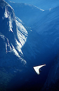 A hang glider soars over Yosemite Valley after launching off Glacier Point.  The sport in the park is allowed and is regulated and monitored by rangers.  July 1989.