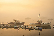 Lobstermen head out on the water during a foggy morning sunrise at Five Islands Harbor, Maine.