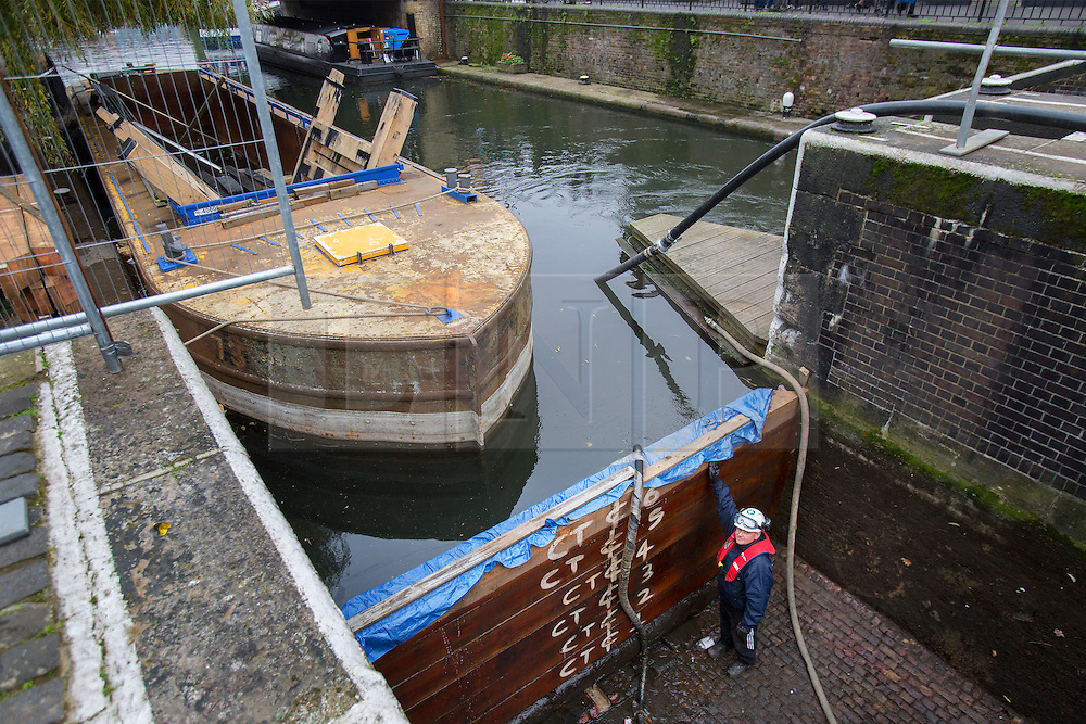 © licensed to London News Pictures. London, UK 17/11/2013. Engineers introducing the bottom of the drained chamber of Camden Lock and the Regent's Canal to members of public visiting. The lock was drained for maintenance as part of a £45million countrywide project. Engineers are replacing both sets of lock gates, as well as carrying out brickwork repairs, repointing and timberwork. Photo credit: Tolga Akmen/LNP