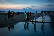 Traditionally dressed Asian men walk along a thin strip of dry sand between two large sea puddles at sunset dusk on Laboni Beach, Cox Bazar, Chittagong Division, Bangladesh, Asia. Their reflections can be seen in the water. <br /> (photo by Andrew Aitchison / In pictures via Getty Images)