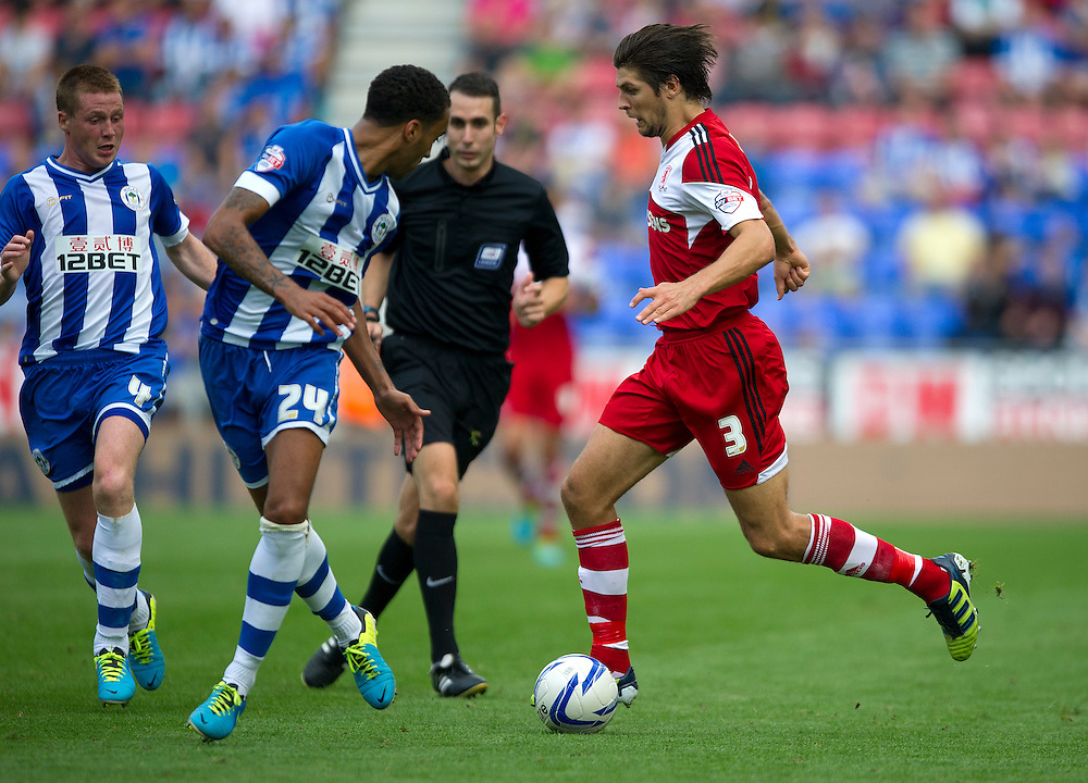 Middlesbrough's George Friend runs at Wigan Athletic's James Perch and James McCarthy (L)<br /> <br /> Photo by Stephen White/CameraSport<br /> <br /> Football - The Football League Sky Bet Championship - Wigan Athletic v Middlesbrough - Sunday 25th August 2013 - DW Stadium - Wigan<br /> <br /> © CameraSport - 43 Linden Ave. Countesthorpe. Leicester. England. LE8 5PG - Tel: +44 (0) 116 277 4147 - admin@camerasport.com - www.camerasport.com