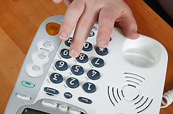 Young person keying in numbers on a special large button telephone,