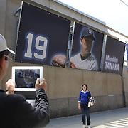 Japanese baseball fans take photographs in front of a billboard of Masahiro Tanaka as they arrive at Yankee Stadium on game day to see Masahiro Tanaka, New York Yankees, pitching during the New York Yankees Vs Tampa Bay Rays, Major League Baseball game at Yankee Stadium, The Bronx, New York. 3rd May 2014. Photo Tim Clayton