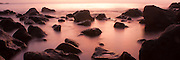 Rocks dot a calm shoreline at sunset on Oahu' north shore, Hawaii