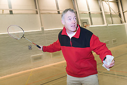 Man playing a game of badminton  in the sports hall of his local leisure centre,