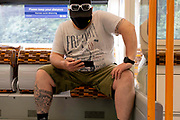 A rail passenger wearing a face covering reads the screen of his phone on an Overground train in south London, on 11th August 2021, in London, England.