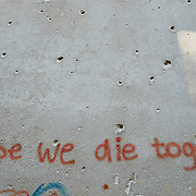 MOSTAR, BOSNIA AND HERZEGOVINA - JUNE 28:  A graffiti is seen on a concrete wall damaged by bulletts from the 1993 war is seen on June 28, 2013 in Mostar, Bosnia and Herzegovina. The Siege of Mostar reached its peak and more cruent time during 1993. Initially, it involved the Croatian Defence Council (HVO) and the 4th Corps of the ARBiH fighting against the Yugoslav People's Army (JNA) later Croats and Muslim Bosnian began to fight amongst each other, it ended with Bosnia and Herzegovina declaring independence from Yugoslavia.  (Photo by Marco Secchi/Getty Images)
