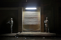 """Capt. Jessie Norton and translator Mushtag """"Mitch"""" Alleathe, keep watch outside an apartment building, as Iraqi soldiers raid a home, Mosul, Iraq, Dec. 12, 2005. This is a joint mission using intelligence from captured insurgent Ahmed Mohammed Ali, also known as Neshuan. Members of the 1st Infantry, 17th Regiment, helped Iraqi forces in preparation for Iraq's first post-Saddam parliamentary elections. The western sector is home to Mosul's primarily Sunni population, which has been resistant to the American presence in Iraq."""