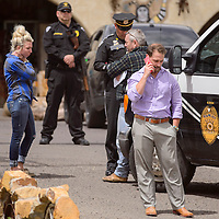 Steve Coleman and his family speak with New Mexico State Police officers outside of The Nugget Gallery in Gallup Tuesday.