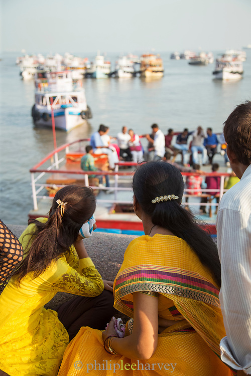 View of Indian Tourists looking out to Mumbai Harbor from Gateway of India, Mumbai, India
