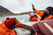 Dariusz Ignatiuk fires a flare gun in celebration and goodbye as he and colleagues pull away from the Polish Polar Station in Hornsund, Svalbard at the end of their field season.