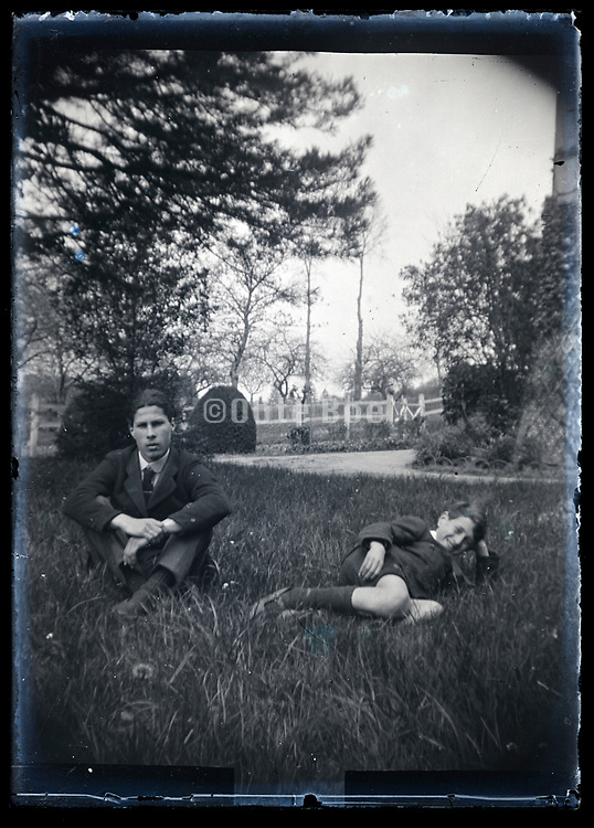 boy and young adult man sitting in the grass France ca 1920s