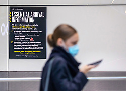 © Licensed to London News Pictures. 15/02/2021. London, UK. A Passenger walks past a Covid-19 government poster reminding people to fill out their Passenger Locator Form for people arriving from red-list countries at London Heathrow Terminal 5 this morning. From today, (Monday 15 February 2021) anyone arriving from a red-list destination must quarantine at a designated hotel and pay a hotel fee of £1,750 for a 10 day quarantine period. Photo credit: Alex Lentati/LNP