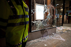 """© under license to London News Pictures. 25/03/2011: Following large anticuts protests across central London, a policeman stands guard outside a branch of Santander, which had its windows smashed by protesters. Credit should read """"Joel Goodman/London News Pictures""""."""