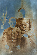 extreme silver mirroring on a vintage studio portrait of two young adult boys wearing a school uniform Japan
