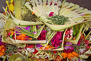Colorful temple offerings made of flowers and rice pile up at a Batur temple shrine.