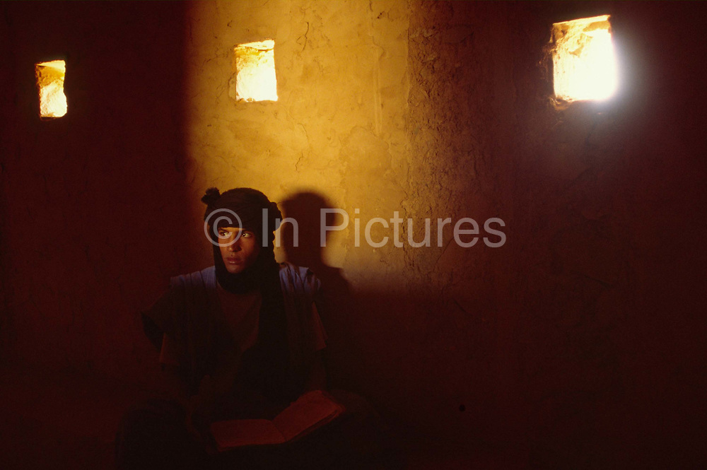 """A boy librarian in an ancient library, in Chinguetti, Mauritania, once one of Islam's holiest cities (today it is regarded as the seventh holiest city) it has been dated at a around seven hundred, (700) years old and is famed for it's Koranic libraries and distinctive mosque, Mauritania. From the story """"The Wind and the City""""."""