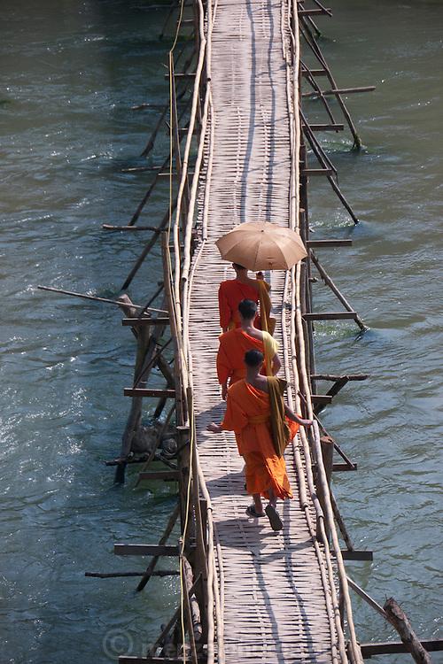 Bamboo bridge across the Nam Khan River, Luang Prabang, Laos. Monks crossing.