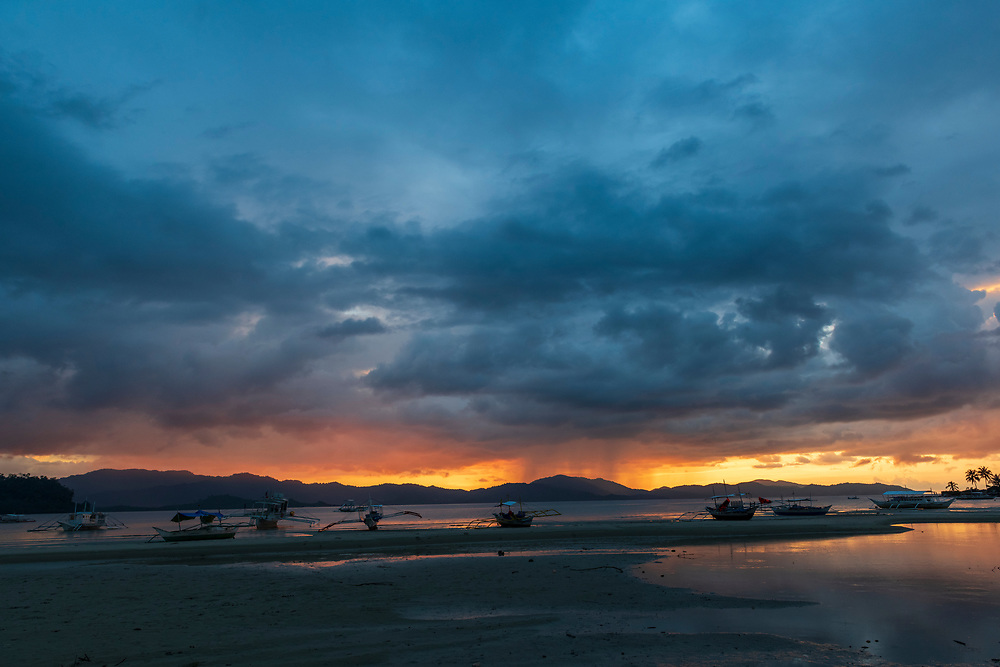 Traditional bangka boats are parked at the beach at sunset in Port Barton, Palawan, Philippines. Rain falls in the distance near the center of the picture.