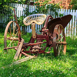Lancaster, PA – July 13, 2016: An old, horse-drawn plow, in a yard near a white picket fence on the grounds of the Landis Valley Village & Farm Museum.