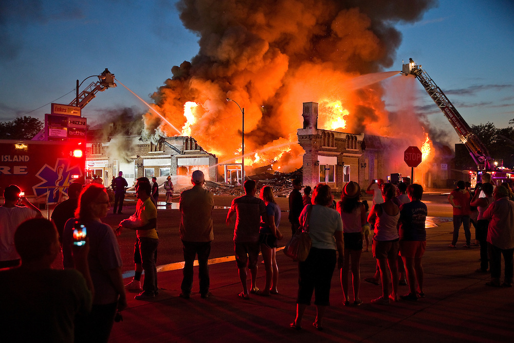 A crowd gathers to watch as firefighters work to control a large fire Sunday at Third and Elm Streets.