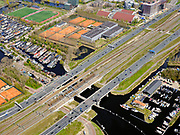 Nederland, Noord-Holland, Amsterdam; 17-04-2021; Zuidas, begin ring A10, A10 Zuid. Zicht op de Schinkelbruggen en de Nieuwe Meersluis. IJsbaanpad met woonschepen, tennisvelden en sporthallen Zuid. Rechtsonder in beeld jachthavens in de Nieuwe Meer. <br /> Zuidas, start of ring A10, A10 South. View of the Schinkel bridges and Nieuwe Meersluis (lock). IJsbaanpad with houseboats and sport centre. Bottom right marinas in the Nieuwe Meer.<br /> <br /> luchtfoto (toeslag op standaard tarieven);<br /> aerial photo (additional fee required)<br /> copyright © 2021 foto/photo Siebe Swart