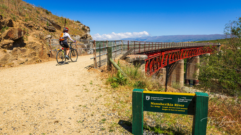 Cyclist crossing the Manuherikia River bridge on the Otago Central Rail Trail, Otago, South Island, New Zealand
