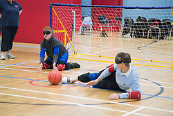 Team Player blocking ball from going into goal during a Goalball game; a threeaside game developed for the visually impaired and played on a volleyball court, A specially adapted ball containing an internal bell is used,