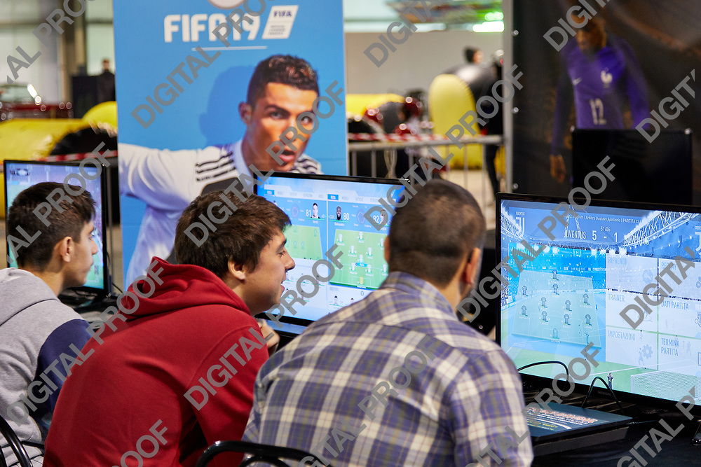 Milan, Italy - March 8 2019 Cartoomics Comic Con Visitors play FIFA 19 EA Sports game with Cristiano Ronaldo poster at the background